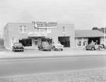"Heishman's Garage. Banner hangs on front of building advertising the ""new 1950 Studebaker."""