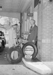 Two men standing outside of the ladie's restroom of a Gulf Service Station next to two tires.