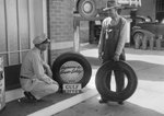 Two men talking at a Gulf Service Station next to a Gulf tire display.