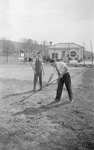 Two men working in a field in front of the Troutville Service Station.