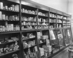 Inside of Everly Drug Store, view of wall shelves containing stuffed animals, feminine products, various medicines, etc.