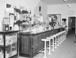 Inside of Dominion Lunch Restaurant, view of counter and bar stools, with various food items for sale behind the counter. New Market, Va. by William Garber