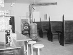 Inside of Dominion Lunch Restaurant, view of booth tables across from the counter, with a heating furnace in the middle of the room and a jukebox in the background. New Market, Va. by William Garber