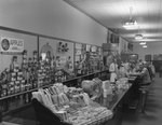 Inside of Walter's Restaurant. View of counter with men on both sides looking towards the camera. Candy bars, cans of apple sauce, and other items can be seen for sale behind the counter. by William Garber