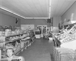"Inside of Mick or Mack ""Cash Talks,"" shelves of food pictured with some shoppers and an employee. by William Garber"