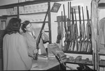 Inside Hodgin's Store, alternate view of a man showing a rifle to a woman. Woodstock, Va. by William Garber