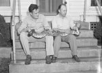 Two men sitting on the front steps of Stroop's Snake Farm holding a large snake. Bowmans Crossing, Va. by William Garber
