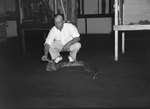 Inside of Stroop's Snake Farm, a man handling a snake on the floor. Bowmans Crossing, Va. by William Garber