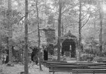 On the grounds of Orkney Springs Hotel, a place for church services or other gatherings. Wooden benches lined up facing a stone platform in the forest. Orkney Springs, Va. by William Garber