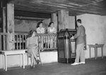 Inside of the Shenandoah Alum Springs Hotel, a group of people sitting and standing, with a man playing a Jukebox. Orkney Springs, Va. by William Garber