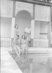 Four people sitting and standing on the edge of the swimming pool at the Shenandoah Alum Springs Hotel. Orkney Springs, Va. by William Garber