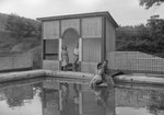 People sitting on the diving board of the swimming pool at the Shenandoah Alum Springs Hotel. Orkney Springs, Va. by William Garber