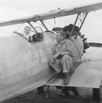 Close up of a man and a boy posing with an airplane, presumably Jack Reynold's plane by William Garber
