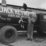 A young boy sitting on the side of a chemical storage truck for Jack Reynold's airplane spraying, a man standing beside him