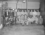 A group of men and women posing in a large storage room of sorts