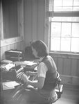 A woman sitting at a desk, typing on a typewriter