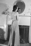 Rear view of a woman in a formal gown looking in a mirror that hangs over a mantle