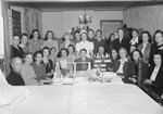 A large group of women posing around a table with various sewing related items