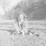 A little girl playing in the grass with a group of puppies, possibly basset hounds