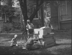 "Three young boys playing in the yard of a home with large boxes that have the inscription ""Glass Do Not Drop"" on the side"
