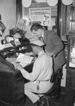 Side/rear view of a man in a work uniform looking at a magazine at a cluttered desk, with a man in a suit looking over his shoulder