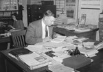 Front view of a man working at a very cluttered desk