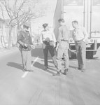 Four men standing behind a tractor-trailer truck