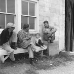 Three men and a young boy sitting on benches outside of a building