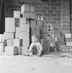 A young boy sitting on the floor in front of a tall stack of boxes