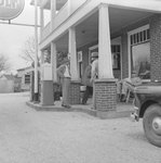 Group of men standing outside of a gas station