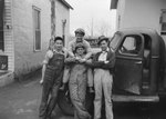 Four men in overalls leaning on the front end of a truck