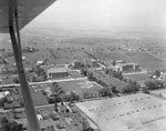 A number of large buildings, probably of the Eastern Mennonite University campus, with the plane obstructing the view. Harrisonburg, Va.