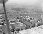 A number of large buildings, probably of the Eastern Mennonite University campus, with the plane obstructing the view. Harrisonburg, Va. by William Garber