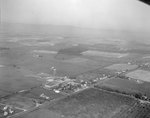 Distant view of private and public buildings surrounded by farmland by William Garber
