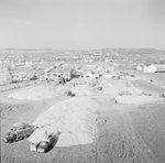 Close up of large trucks loading or unloading a large pile of gravel or dirt by William Garber