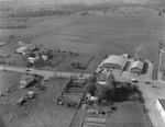 A number of public buildings with fields and a wooded area in the background by William Garber