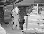 Inside Mt. Jackson Mill, man carrying a sack of hog ration.