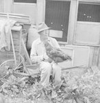 Man holding a chicken at the Mt. Jackson Mill. by William Garber