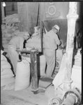 Two men working inside the Mt. Jackson Mill. by William Garber