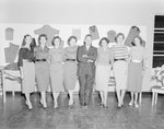 New Market Manufacturing, a man posing with seven women in front of a display of articles of clothing.