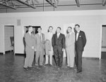 New Market Manufacturing, six men in suits posing in a bare room. by William Garber