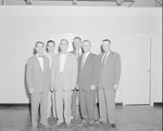 New Market Manufacturing, six men in suits posing in a bare room.