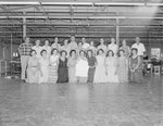 New Market Manufacturing, large group of men and women posing in a room full of sewing machines and other equipment.
