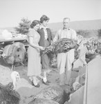 A man and two women examining a turkey.