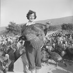 A woman holding a turkey as she stands in a large group of turkeys.