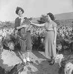 Two women standing among a large group of turkeys: one holds a turkey.
