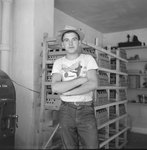 A man standing in front of crates of, presumably, baby chickens. by William Garber
