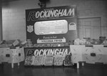 "Close up view of a ""Genuine Rockingham Virginia Poultry"" display, set up for a fair or other kind of show/presentation. Sponsored by Rockingham Plants in Broadway, Va., and advertising ""Ready to Cook Virginia Fryer"". by William Garber"