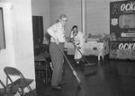 A Rockingham poultry display with two men sweeping the floor area in front. by William Garber