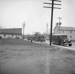 Distant view of a line of school buses parked on the street by William Garber